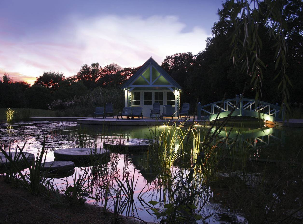 Boat house on a natural pool at private house in Dulwich, garden designed by Kristina Fitzsimmons and lit by Mike Shackleton of Ornamental Garden Lighting