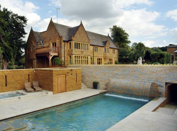 A new house in the Cotswolds by Janine Stone, built in period style. The swimming pool is set low so as not to interfere with the views.