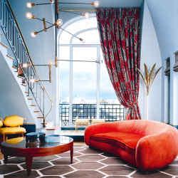 A Parisian apartment by DimoreStudio, with DimoreStudio metal and brass Lampada light, price on request, vintage Jean Royère sofa, Jim Thompson Golden Sunburst curtain fabric andantique kilim