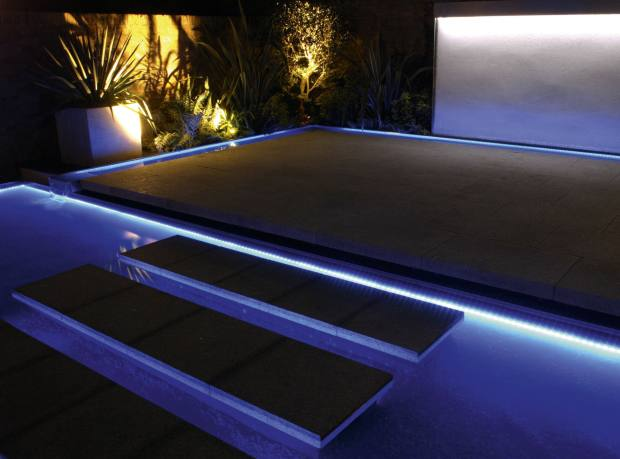 A water feature with lighting by Robert Webber in a garden designed by Philip Nash