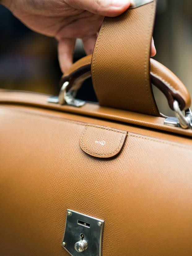 Each briefcase is made from a single piece of skin with a stylish brass bar clasp folding neatly over the handle