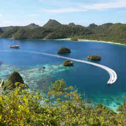The Lamina moored just off the island of Wayag in northern Raja Ampat, Indonesia, with its tender bringing guests to the beach.