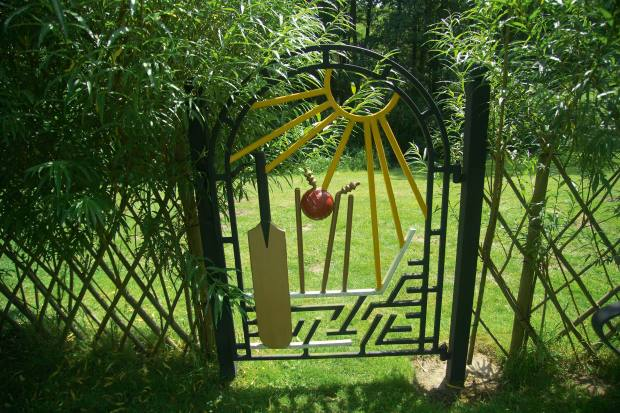 The gate of a Fisher-designed cricket-themed willow hedge maze in Hampshire that reflects the owner's love of cricket
