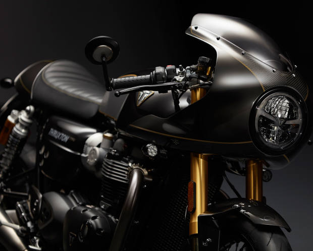 The motorcycle's carbon black paintwork is highlighted by handpainted pin lines and other gold detailing
