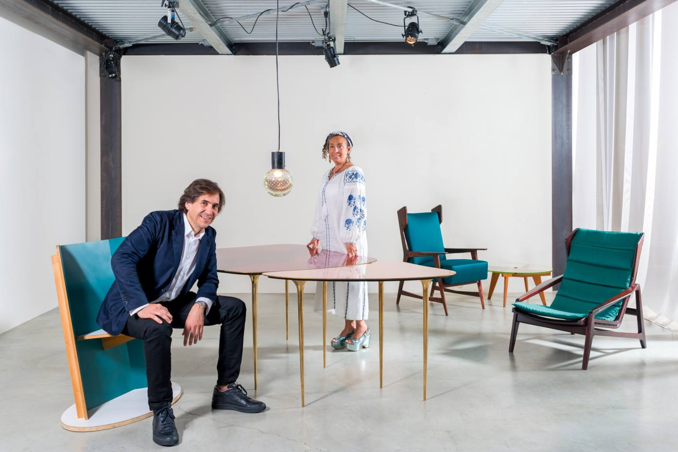 Property developer Karim Abillama and gallerist Nina Yashar in her Milan space, Nilufar Depot. Abillama sits on a Giò Ponti chair reinterpreted by Martino Gamper. Yashar stands at a dining table by Massimiliano Locatelli. Behind her are 1950s wood and cotton/satin armchairs and a wood and glass coffee table, all by Ponti