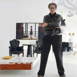 Marcel Wanders in his Amsterdam studio surrounded by his own designs and a selection from Moooi, the company he founded and of which he is artistic director. To the left are the new wine glasses and decanter he designed for Baccarat on the Pizzo Carrara table, one of the Marcel Wanders Personal Editions. To the right are Wanders' iconic Knotted Chairs for Cappellini; his Delft Blue carpet for Moooi; and his new deer-design candlestick for Baccarat, Les Esprits des Bois.