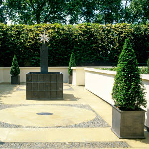 A Park Lane courtyard designed by George Carter, with a Portuguese laurel hedge and yew pyramids