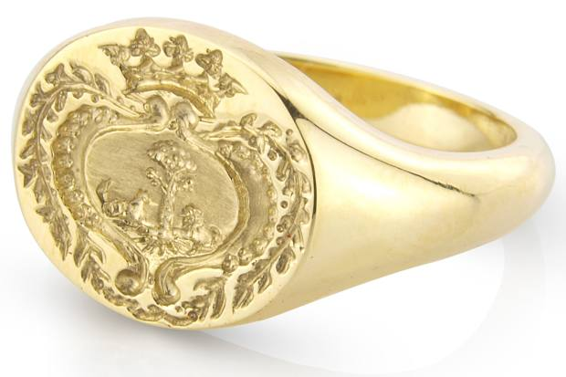 An elaborate tree engraving on a yellow-gold signet ring