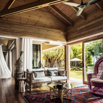 The timber-and‑glass Sunset Suites at the Four Seasons Resort on Desroches Island