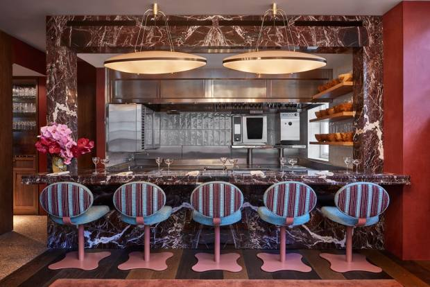 The interior, designed by Rebecca Korner, features rich woods and marbles in jewel tones
