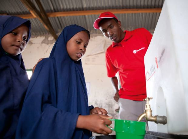 Abdifatah Adow, the charity's hygiene promoter, watches a student testing the new clean drinking water facility in Habaswein, Kenya