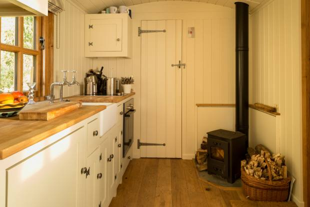 A Living Hut featuring a kitchen and woodburner