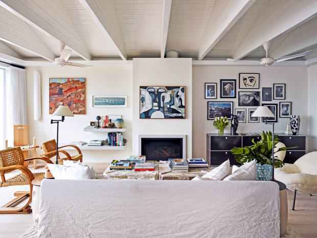 A Gervasoni sofa and Philip Arctander cloud chair sit below the couple's contemporary art collection, including a Kirsty Budge above the fireplace