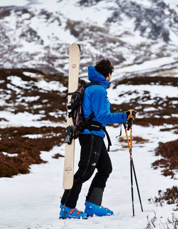 Jamie Kunka, of Lonely Mountain Skis, carrying Sneachda skis (from £750) at Carn an Tuirc in the Scottish Grampians