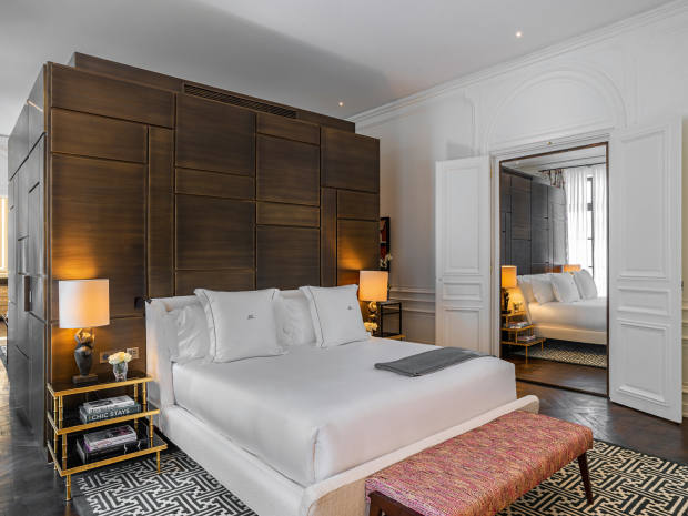 One of the bedroom suites at JK Place Paris, with a massive bronze box dividing the space