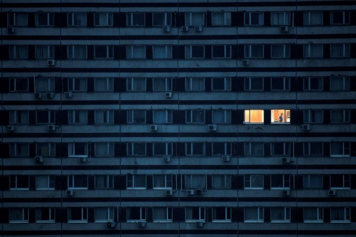 A man is pictured in an illuminated apartment in a building